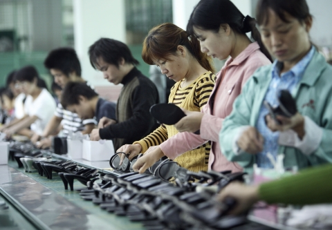 Workers labor on the production line for women's shoes at the Junsheng Shoe factory in Dongguan, China. (Photographer: Qilai Shen/Bloomberg News)