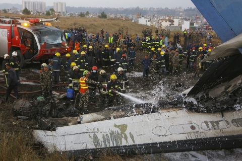 Nepalese firemen spray water on the debris after a passenger plane from Bangladesh crashed at the airport in Kathmandu, Nepal, Monday. (Source: PTI)