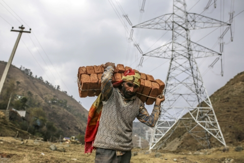 A worker carries a bundle of bricks on his back past a Sterlite Power Transmission Ltd. transmission tower in Rajouri district, Jammu and Kashmir, India. (Photographer: Dhiraj Singh/Bloomberg)