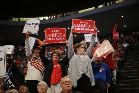 "Attendees hold ""Make America Great Again"" signs during a campaign event for Donald Trump on Oct. 13, 2016. (Photographer: Luke Sharrett/Bloomberg)"