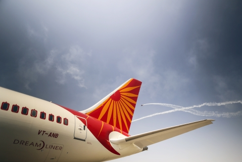 Planes fly past a Boeing Co. 787 Dreamliner aircraft, operated by Air India. (Photographer: Dhiraj Singh/Bloomberg)