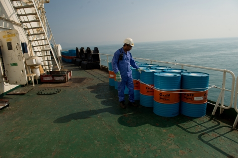A crew man secures Gulf Marine oil drums on the deck of oil tanker 'Devon' as it prepares to transport crude oil from Kharq Island to India in Bandar Abbas, Iran (Photographer: Ali Mohammadi/Bloomberg)