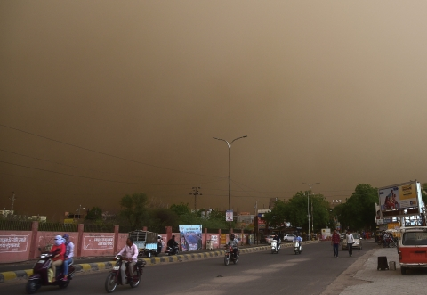 Vehicle ride past on a road during a dust storm in Bikaner on Wednesday. (Source: PTI)