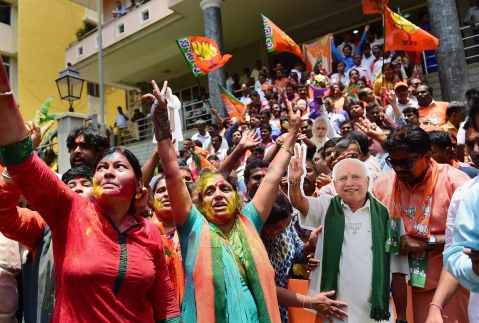BJP workers, with a cut-out of chief ministerial candidate BS Yeddyurappa, celebrate the party's lead on more than 110 Assembly seats, as the counting of votes is in progress, outside the party office in Bengaluru. (Source: PTI)