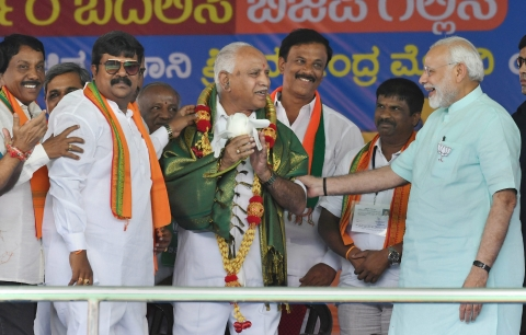 Prime Minister Narendra Modi and BJP's chief ministerial candidate BS Yeddyurappa share a lighter moment during Karnataka election campaign rally at Chamarajanagar. (Photograph: PTI)
