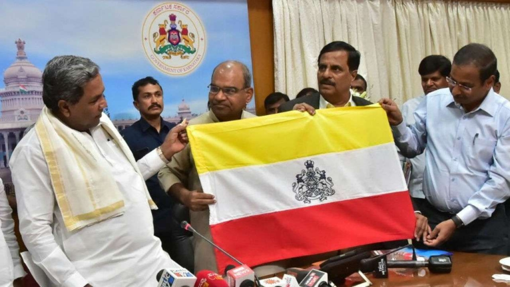 Chief Minister Sidaramaiah unveils the Karnataka flag. (Source: Twitter/INC).