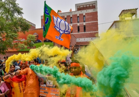 BJP workers celebrate the party's lead during counting of votes for Karnataka Assembly elections, at the party headquarters in New Delhi. (Photographer: Manvender Vashist/PTI)