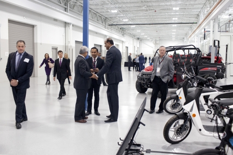 Attendees walk past vehicles at the Mahindra Automotive North America facility in Auburn Hills, Michigan, U.S., on Nov. 20, 2017. (Photographer: Laura McDermott/Bloomberg)