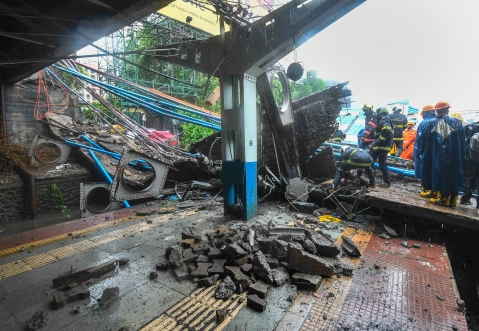 Rescue workers clear the debris of Gokhale foot overbridge that collapsed on the Western Railway tracks, at Andheri station following heavy rain. (PTI Photo/Shirish Shete)