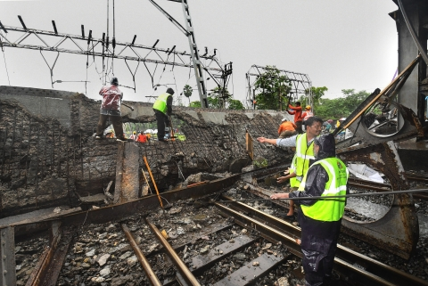 Rescue workers clear the debris of Gokhale foot overbridge that collapsed on the Western Railway tracks, at Andheri station following heavy rain, in Mumbai on Tuesday, (Photographer: Shirish Shete/PTI)