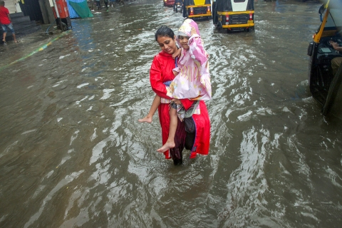 A woman, carrying a girl, makes her way through a waterlogged road during heavy rains in the city. (Source: PTI)