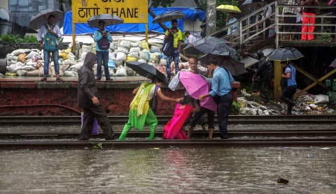 A woman is helped by other commuters after she falling on the tracks at  Thane Railway Station during heavy rains, in the city. (Source: PTI)
