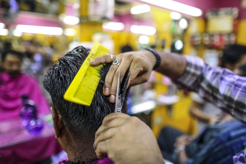 A customer gets a haircut at a barber's shop in Bangalore, India(Photographer: Dhiraj Singh/Bloomberg)