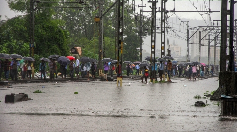 Commuters wade through flooded tracks in Thaneat the railway station. (PTI)
