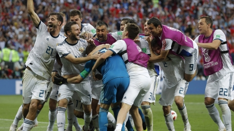 Russian players mob Russia goalkeeper Igor Akinfeev, front left in blue, after Russia defeated Spain by winning a penalty shoot in the round of 16 match between Spain and Russia at the 2018 FIFA World Cup at the Luzhniki Stadium in Moscow, on July 1, 2018. (Photograph: AP/PTI)