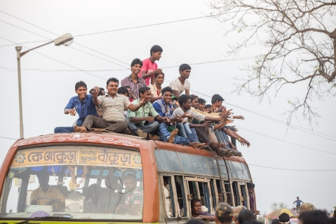 Supporters of a political party sit on the roof and in a bus after an election rally in Bankura, West Bengal. (Photographer: Prashanth Vishwanathan/Bloomberg)