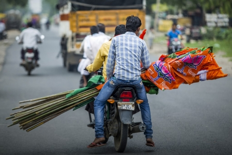 BJP supporters carry the party's flag during a BJP motorcycle rally. (Photographer: Prashanth Vishwanathan/Bloomberg)
