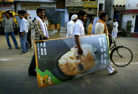 A BJP supporter carries a picture of then  Prime Minister Atal Bihari Vajpayee after an election rally in Aligarh, Uttar Pradesh on  April 29, 2004. (Photographer: Amit Bhargava/Bloomberg News)