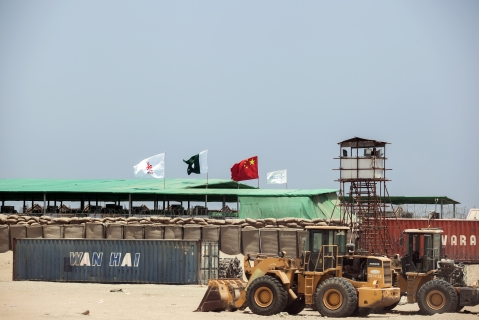 A  shipping container sits beyond an excavator outside a workers camp, operated by China Overseas Ports Holding, in Gwadar, Balochistan, Pakistan, on  July 4, 2018. (Photographer: Asim Hafeez/Bloomberg)