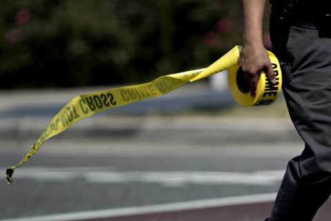A police office carries crime scene tape in Alexandria, Virginia, U.S. (Photographer: Andrew Harrer/Bloomberg)