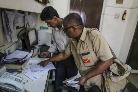 Jitendra Rana, a mail carrier for India Post, delivers mail to an office in Mumbai. (Photographer: Dhiraj Singh/Bloomberg)