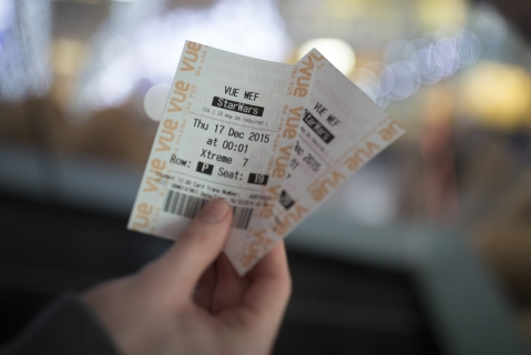 "A customer holds his tickets to view the first public screening of Walt Disney's ""Star Wars: The Force Awakens"" on Dec. 16, 2015. (Photographer: Simon Dawson/Bloomberg)"