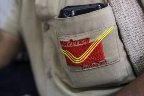 The India Post logo is seen on the shirt of a mail carrier in Mumbai, India. (Photographer: Dhiraj Singh/Bloomberg)