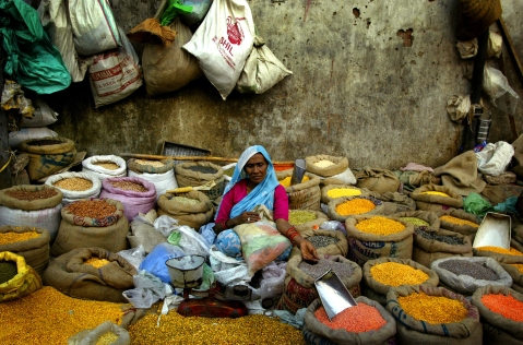 A woman sells pulses near a wholesale market in an old section of New Delhi. (Photographer: Amit Bhargava/Bloomberg News)