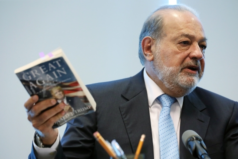Billionaire Carlos Slim, chairman emeritus of America Movil SAB, speaks while holding up U.S. President Donald Trump's book, in Mexico City, Mexico, on  Jan. 27, 2017. (Photographer: Susana Gonzalez/Bloomberg)