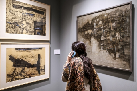 A visitor talks on the phone as she looks at paintings during the preview show of Christie's South Asian Art auction in Mumbai. (Photographer: Dhiraj Singh/Bloomberg)