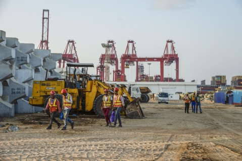 Workers walk past excavators at the site of Colombo Port City, developed by China Harbour Engineering Co. (Photographer: Atul Loke/Bloomberg)