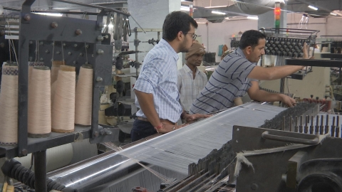 Bhavin Chaudhary supervises  an employee arranging threads on the the yarn. (Photo: BloombergQuint)