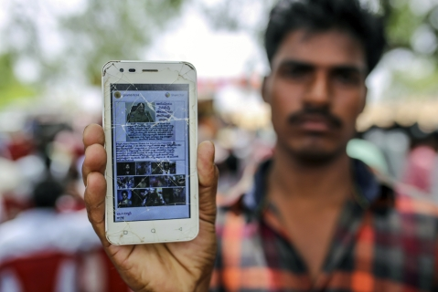 A user  holds a mobile phone displaying a fake message shared on WhatsApp in Gadwal, Telangana. (Photographer: Dhiraj Singh/Bloomberg)