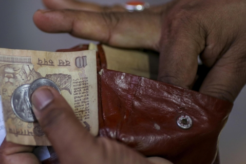 A man takes an Indian ten rupee banknote and one rupee coins out of a wallet in Mumbai. (Photographer: Dhiraj Singh/Bloomberg)