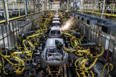 Robotic arms weld panels of automobiles on a production line. (Photographer: Akos Stiller/Bloomberg)