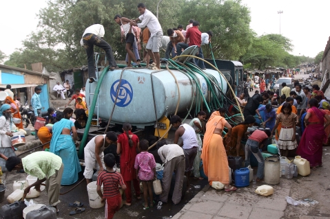 Residents of a poor area fill containers from a government water supply tank, in New Delhi, India. (Photographer: Pankaj Nangia/Bloomberg)