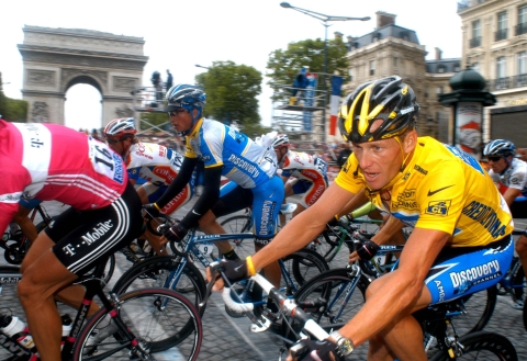 Lance Armstrong rides in front of the Arc de Triomphe on the Champs-Elysees while winning the Tour de France in Paris in 2005. (Photographer: Alastair Miller/Bloomberg News).