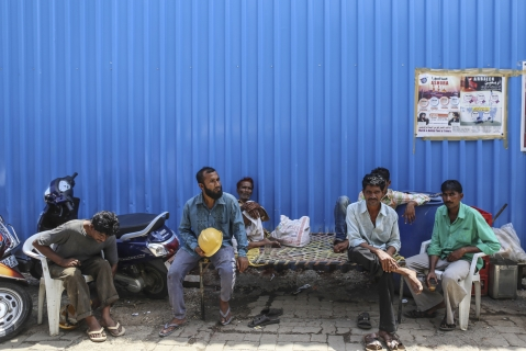 Construction workers sit at a perimeter fence in the Bhendi Bazaar area of Mumbai. (Photographer: Dhiraj Singh/Bloomberg)