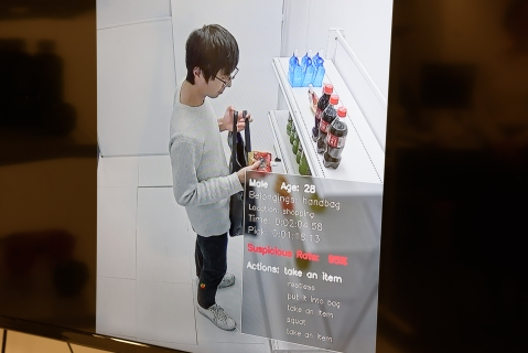 A screen shows a Vaak employee handling a product in a mock store (Photographer: Akio Kon/Bloomberg)