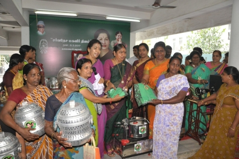 AIADMK party workers hand out cookers, grain mixers, sarees, and sewing machines. (Photograph: Twitter/@AIADMKOfficial)