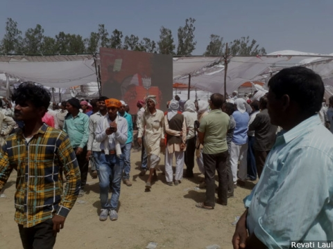 People watch Prime Minister Narendra Modi on a screen as he speaks at a gathering of more than 200,000 people in Uttar Pradesh's Hardoi town. Two-and-a-half centuries after the British annexed Awadh citing Muslim misrule, Modi makes out a case of opposition misrule in the region.