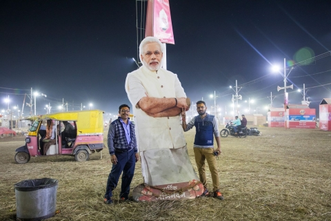 Pilgrims with a cutout of Modi. (Photographer: Anshika Varma for Bloomberg Businessweek)