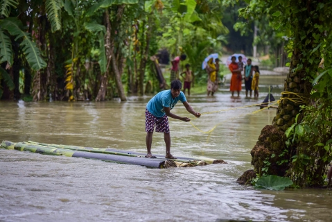 A man rows a makeshift raft to cross floodwaters following incessant monsoon rainfall, at Lahorighat village in Morigaon (Source: PTI)