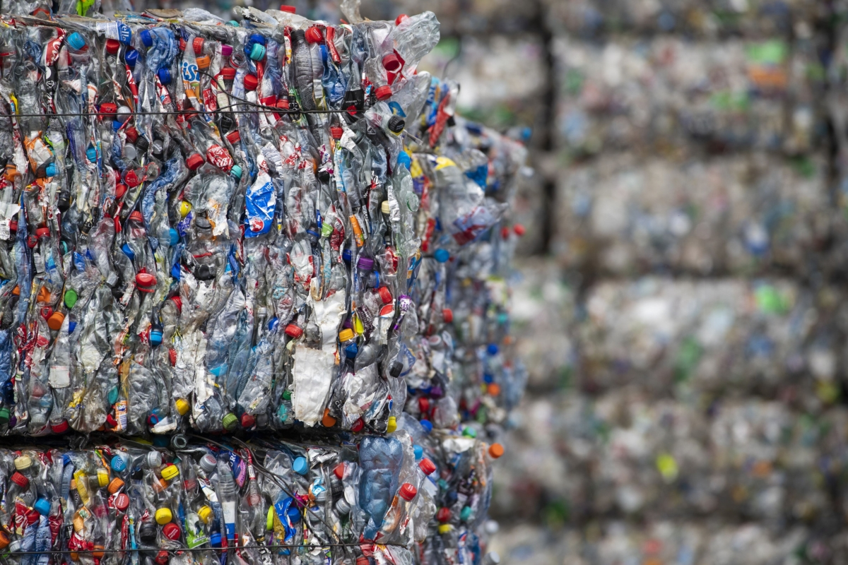 Bound bales of crushed plastic bottles and containers sit stacked ready to be recycled at a recycling centre. (Photographer: Jasper Juinen/Bloomberg)