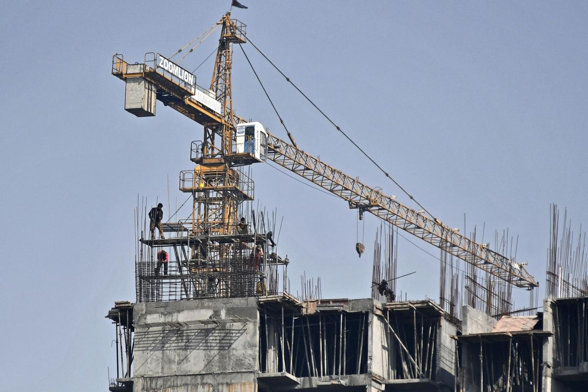 A crane operates on a residential building under construction at an Mahagun India Ltd. development in Noida, Uttar Pradesh, India. (Photographer: Anindito Mukherjee/Bloomberg)