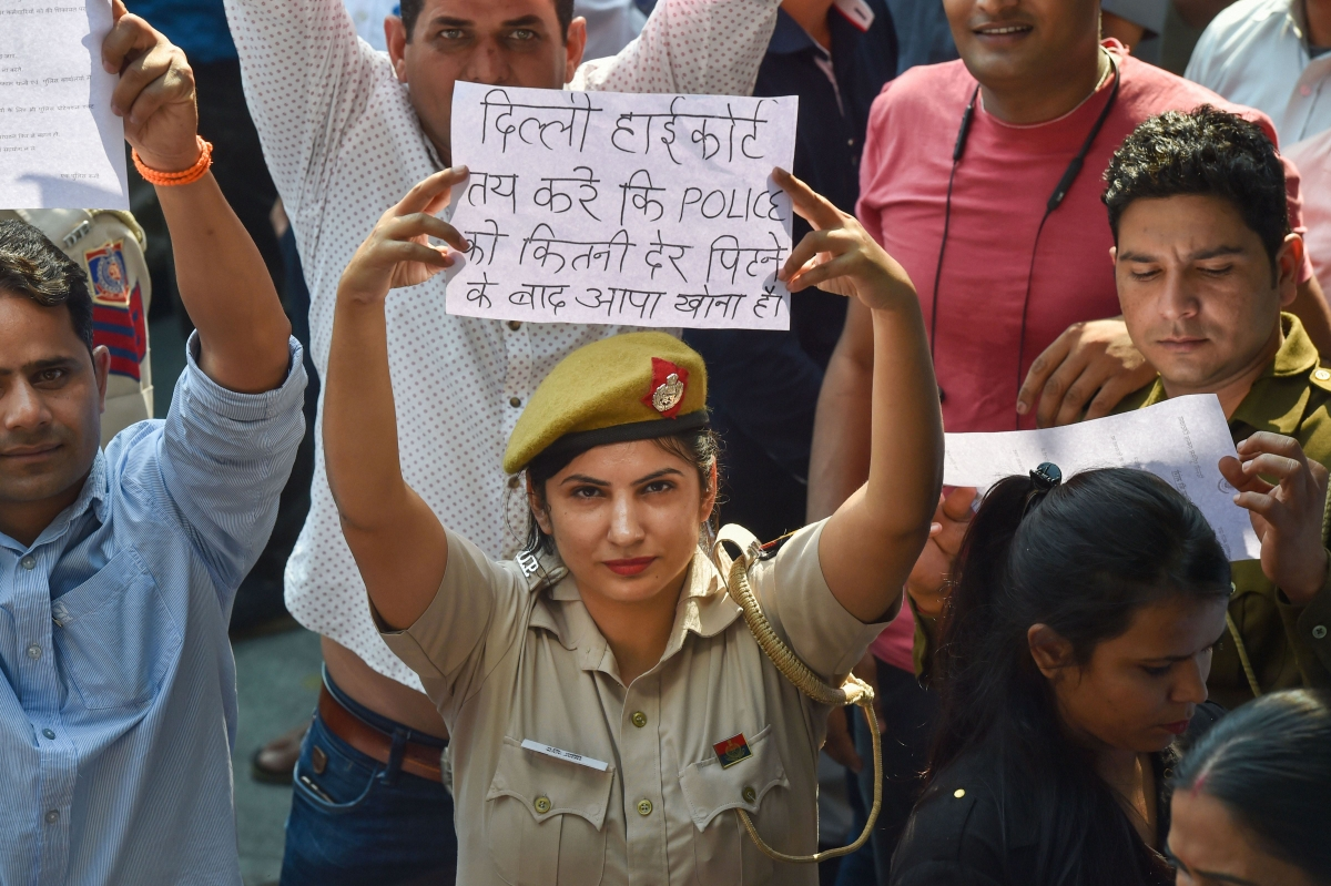 A Delhi Police woman displays a placard during a protest (Source: PTI)