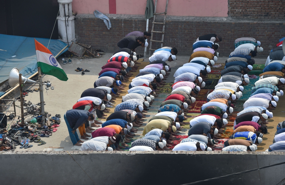 Muslims offer Friday prayers on the rooftop of a mosque, which was burnt by rioters (Source: PTI)