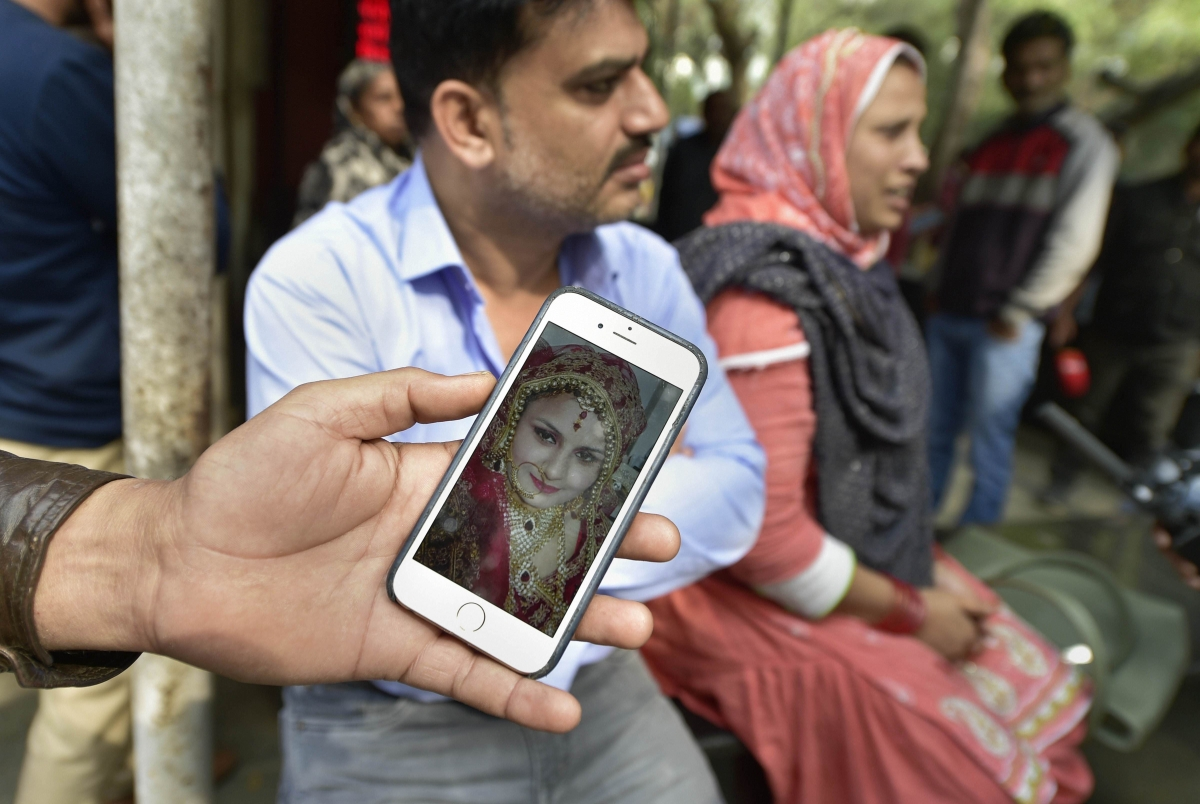 A relative shows a photograph of Tasneem Fatima, wife of Ashfaq Hussain (22), who was killed during the Delhi violence, outside the mortuary of GTB hospital in New Delhi on Thursday, Feb 27, 2020. (Photo: PTI)