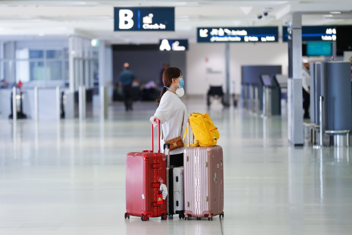 A passenger wearing a protective mask stands with her luggage in a departures hall at Sydney Airport in Sydney, Australia, on Tuesday, March 17, 2020. (Photographer Brendon Thorne/Bloomberg)