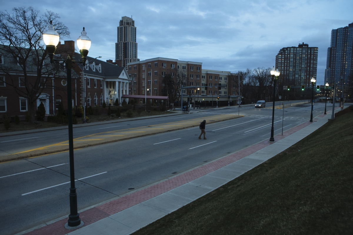 A pedestrian crosses an empty street in New Rochelle, New York, U.S., on Monday, March 16, 2020. The governors of New York, New Jersey and Connecticut banned all gatherings of 50 or more people, and said bars, restaurants, casinos and gyms must close Monday at 8 p.m. (Photographer: Angus Mordant/Bloomberg)